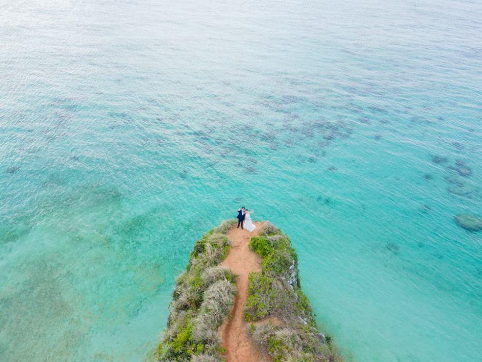 沖縄県恩納村にある「ざねー浜」の崖で、ドローンを使って撮影したブライダルフォト